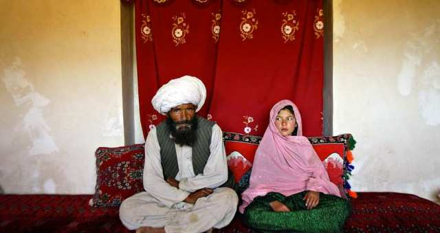 Faiz, 40 (left), and Ghulam (right), 11, sit in her home prior to their wedding in the rural Damarda Village, Afghanistan on September 11, 2005