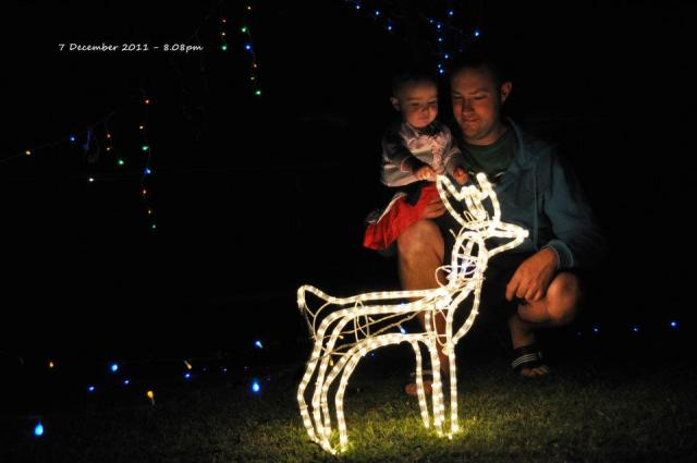 "7 December 2011 - Christmas has always been my favourite time of the year, but this year is just a little bit more special. Our little girl is old enough now to really enjoy the whole experience. She thinks that Gamma and Grandpop's lights are just the best thing. We pull up in the street and she just says ""wow, wow, priddy, priddy,(pretty) wow"" so much that she doesn't even breathe properly. This photo is so special to me because it shows my two favourite people enjoying a gorgeous moment together.."